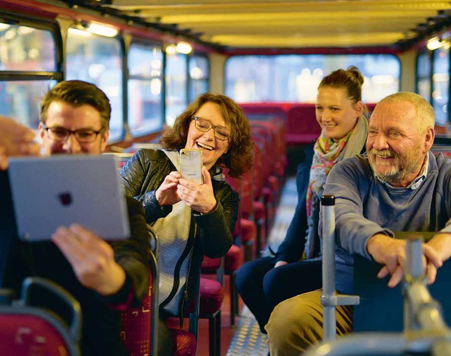 Kleine Rundfahrt: Sascha Albertsen führt die Hamburg App vor, Heinrich Schuster (r.) besitzt aber kein Smartphone. Nachrichten schreibt ihm Katharina Fest (2. v. r) auf gelbe Zettel