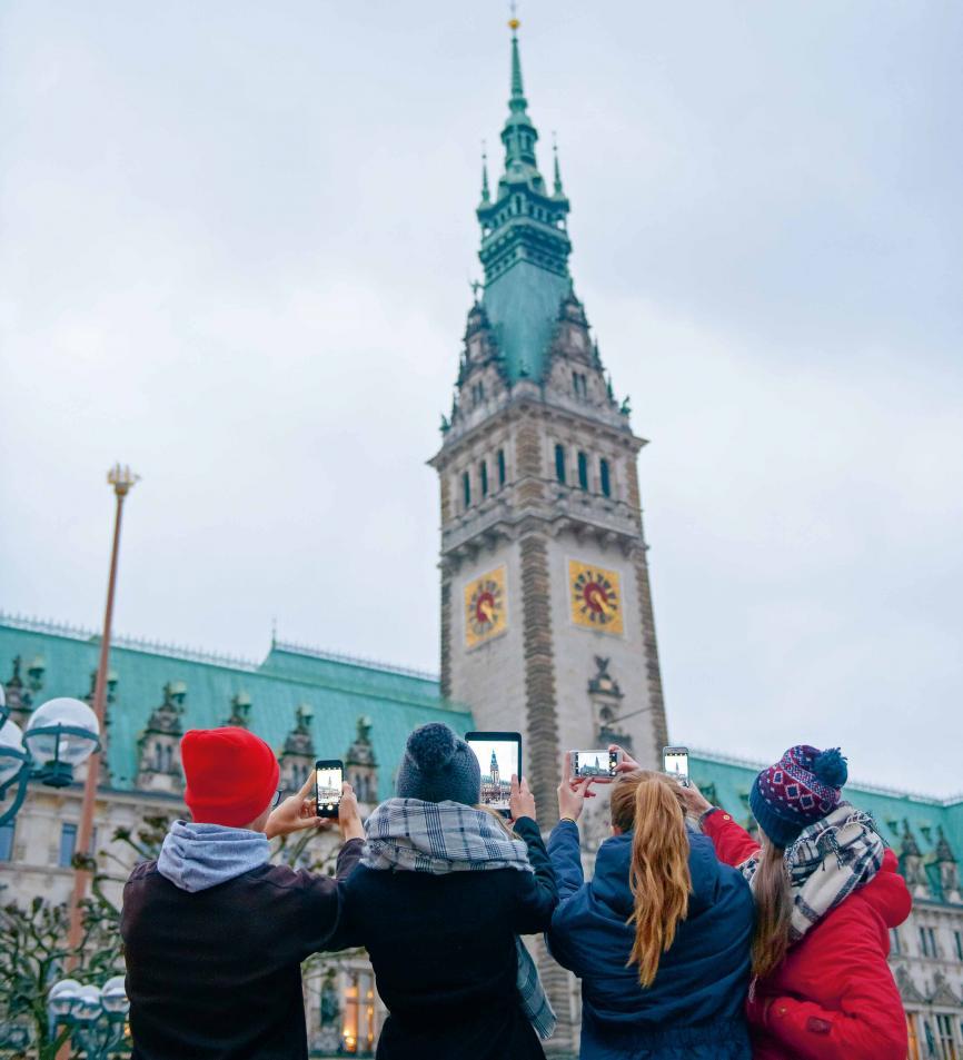 """Rathaus, bitte lächeln!Infos zu Sehenswürdigkeiten, virtuelle Rundgänge und nebenbei den kürzesten Weg zur nächsten Burgerbude checken – alles möglich in unserer digitalisierten Welt. Nicht umsonst sitzen Firmen wie Google, Facebook und Twitter in Hamburg. Natürlich machen Touristen jede Menge Fotos, um sie zu posten, zu sharen und der Welt zu sagen: """"Guck mal, ich bin hier!"""""""